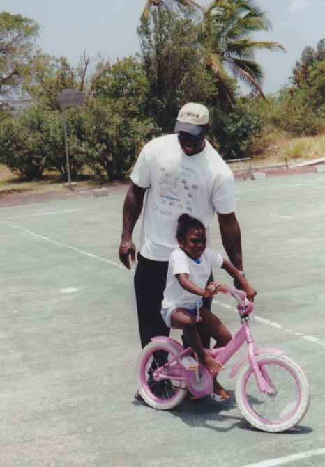 A dad helping his daughter learn how to ride her bike in St. Maarten.
