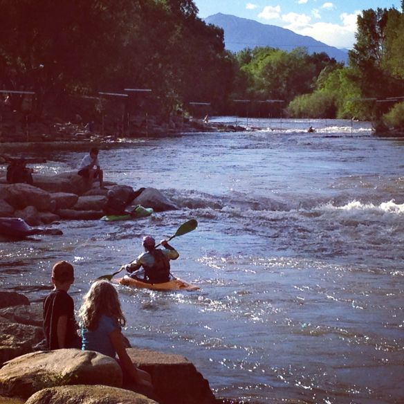 Kids watch kayakers play in Arkansas River in Salida, CO, 2013