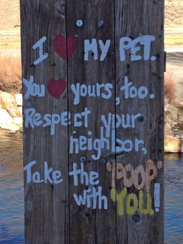A friendly clean up your dog's poop sign