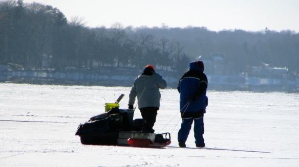 ice fishermen dragging sleds