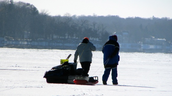 ice fishermen dragging sleds