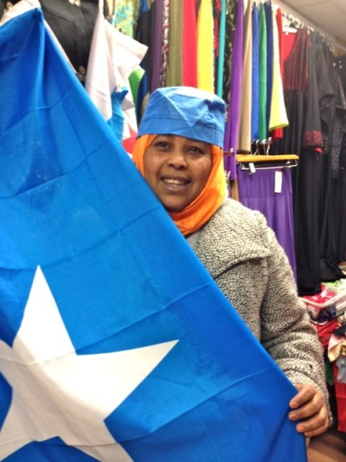 Maryan happily poses for me with the Somali flag and a Somali hat