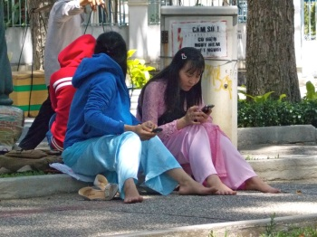 women in ao dais sitting on curb