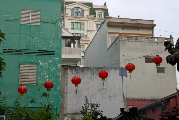 red lanterns against green building in saigon
